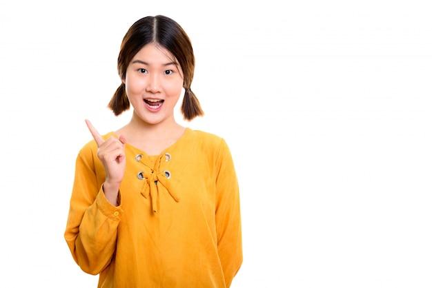 Giovane donna asiatica felice sorridente mentre punta il dito verso l'alto
