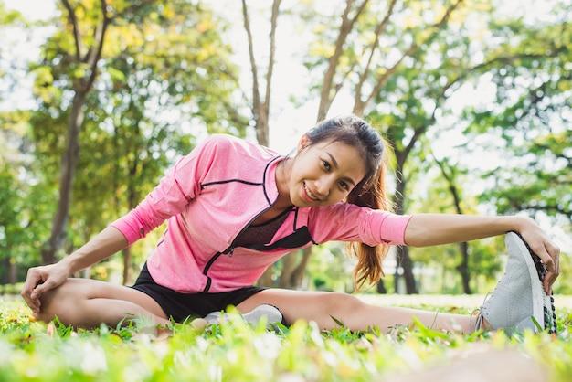 Giovane donna asiatica in buona salute che si esercita al parco. giovane donna adatta che fa allenamento di allenamento in mattinata
