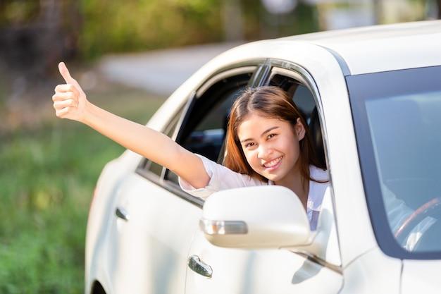 Giovane donna asiatica in camicia bianca alla guida della sua auto e mostrando i pollici