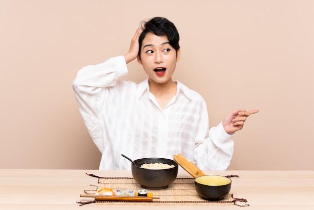 Giovane donna asiatica in un tavolo con ciotola di noodles e sushi sorpreso e puntando il dito verso il lato
