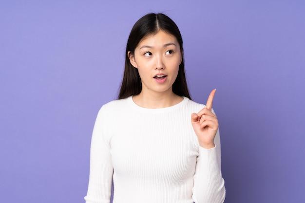 Giovane donna asiatica isolata su spazio viola che pensa un'idea che indica il dito su