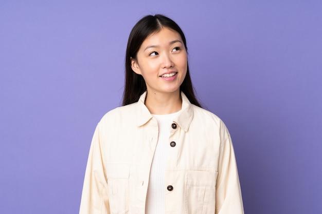Giovane donna asiatica isolata su spazio viola che pensa un'idea mentre osservando in su
