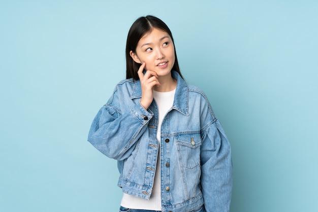 Giovane donna asiatica isolata sulla parete che pensa un'idea mentre osservando in su