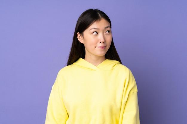 Giovane donna asiatica isolata sulla parete viola che ha dubbi mentre osserva in su