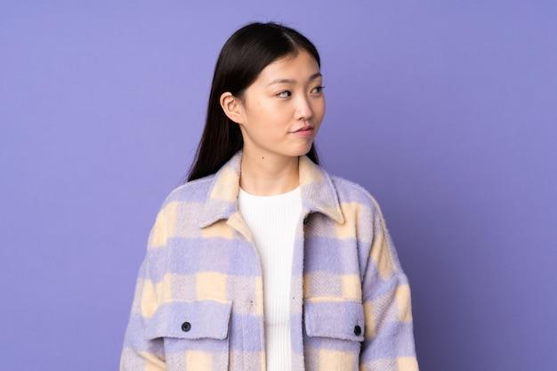 Giovane donna asiatica isolata sulla parete viola che ha dubbi mentre osservando lato
