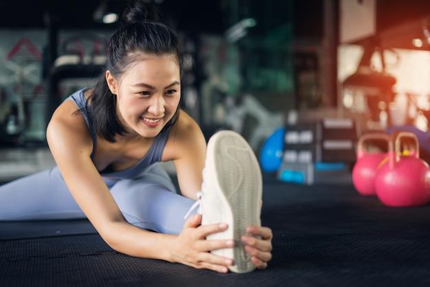 Giovane donna asiatica nello stile di vita sano della palestra che si siede sul piedino della holding della stuoia di yoga che allunga piedino.