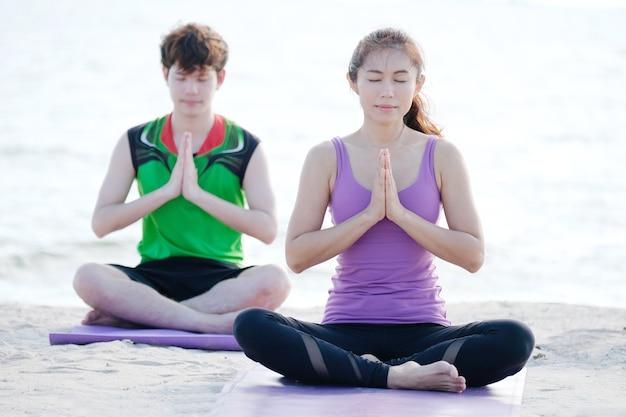 Giovane donna asiatica sana e uomo praticare yoga