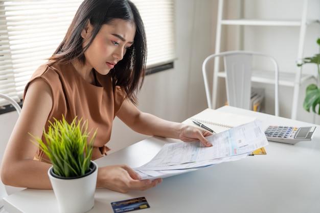 Giovane donna asiatica sollecitata nessun denaro per pagare il debito che guarda le spese mensili di spese sul tavolo