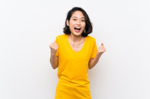 Giovane donna asiatica sopra fondo bianco isolato che celebra una vittoria nella posizione del vincitore