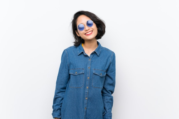 Giovane donna asiatica sopra fondo bianco isolato con occhiali e felice