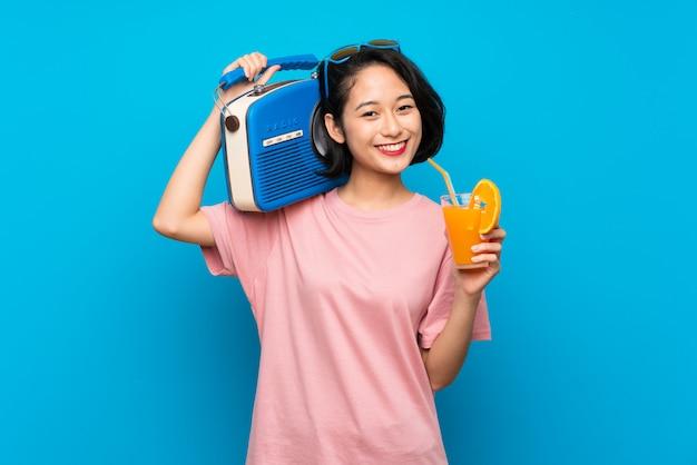 Giovane donna asiatica sopra la parete blu isolata che tiene una radio