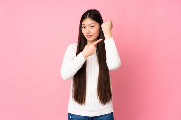 Giovane donna asiatica sopra la parete che fa il gesto di essere in ritardo