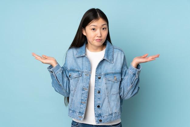 Giovane donna asiatica sopra la parete che ha dubbi mentre solleva le mani