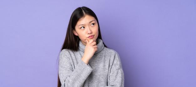 Giovane donna asiatica sopra la parete che ha dubbi