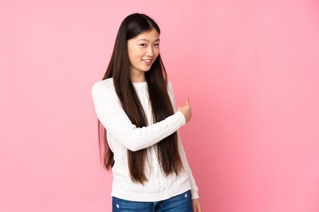 Giovane donna asiatica sopra la parete che indica indietro