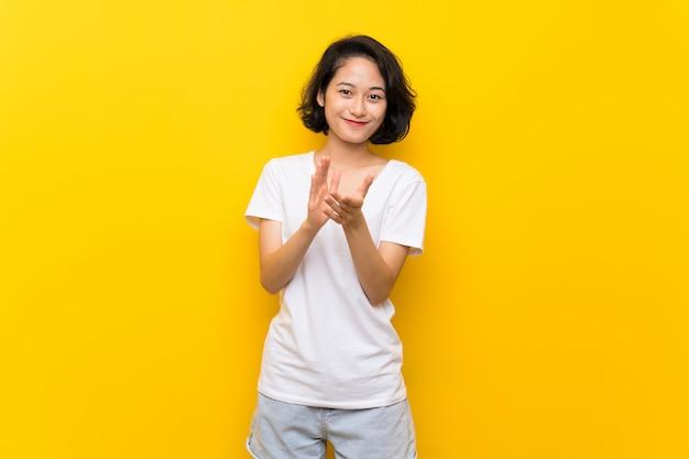 Giovane donna asiatica sopra la parete gialla isolata che applaude dopo la presentazione in una conferenza
