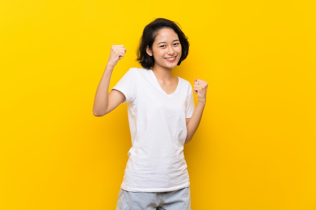 Giovane donna asiatica sopra la parete gialla isolata che celebra una vittoria