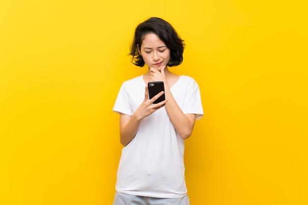Giovane donna asiatica sopra la parete gialla isolata che pensa e che invia un messaggio