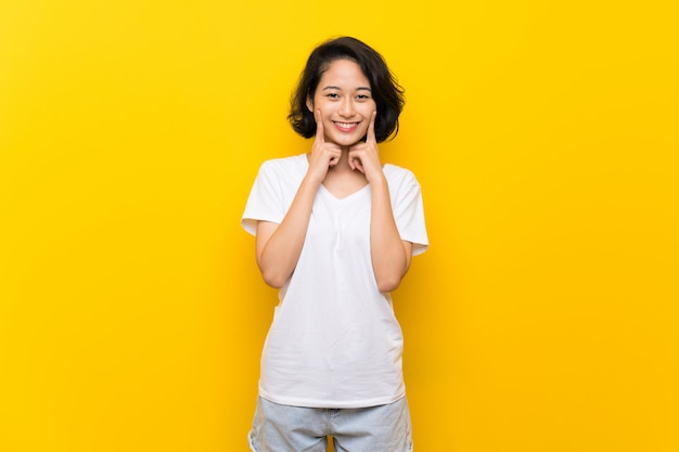 Giovane donna asiatica sopra la parete gialla isolata che sorride con un'espressione felice e piacevole