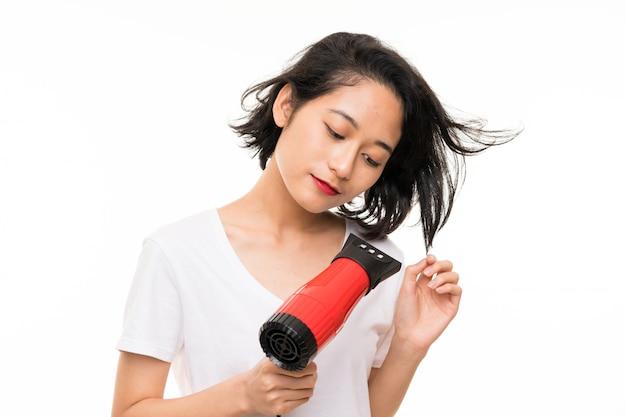 Giovane donna asiatica sopra la parete isolata con asciugacapelli
