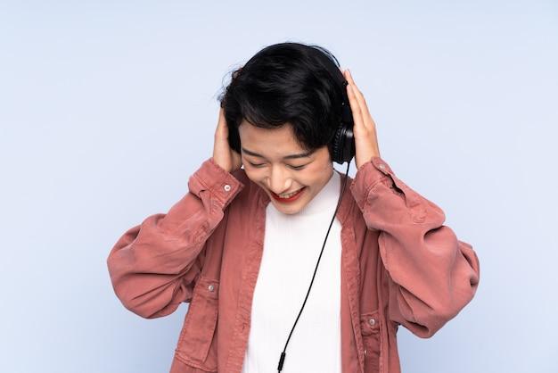 Giovane donna asiatica sopra musica d'ascolto isolata della parete blu