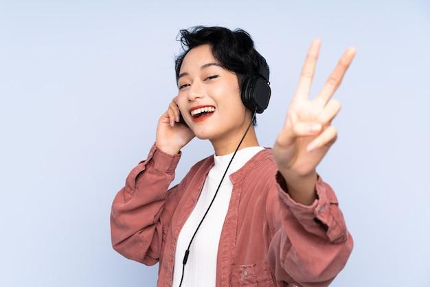 Giovane donna asiatica sopra musica d'ascolto isolata e cantare della parete blu
