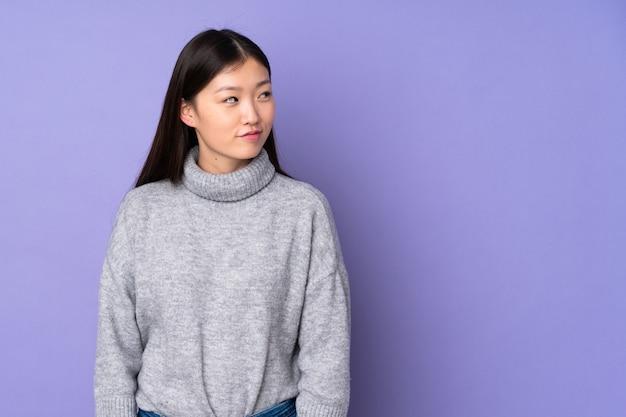Giovane donna asiatica sopra spazio isolato che ha dubbi mentre osservando lato