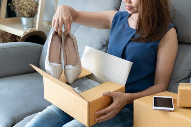 Giovane donna asiatica sorridente che esamina la sua nuova scarpa del tacco alto e che si siede sul sofà a casa, stile di vita digitale con tecnologia, commercio elettronico, concetto online di compera