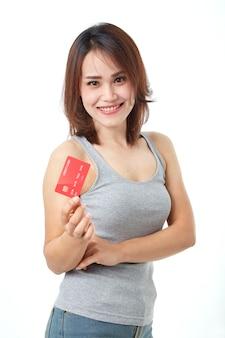 Giovane donna asiatica sorridente che presenta la carta di credito