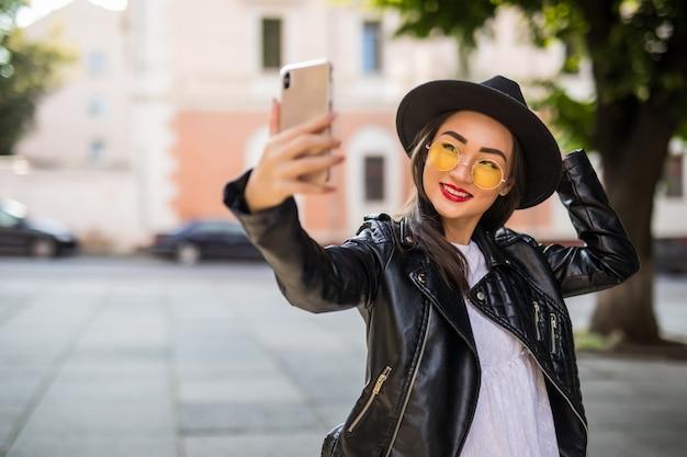 Giovane donna asiatica sorridente in occhiali da sole che prendono selfie sulla via della città