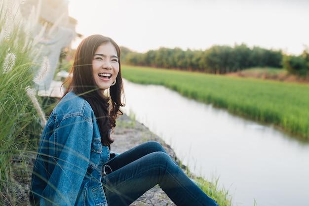 Giovane donna asiatica sorridente. ragazza che gode della bellissima natura con il tramonto.