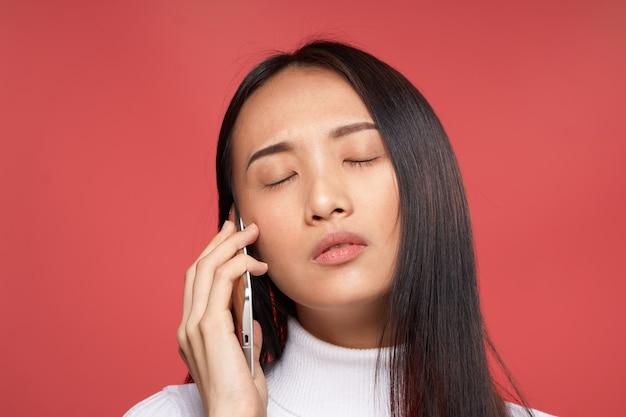 Giovane donna asiatica su uno sfondo blu in posa, emozioni diverse, mock up