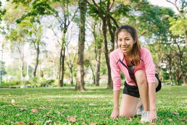 Giovane donna asiatica sul segno di impostare pronto per fare jogging