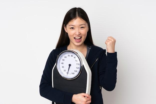 Giovane donna asiatica sulla parete bianca con bilancia e facendo il gesto di vittoria
