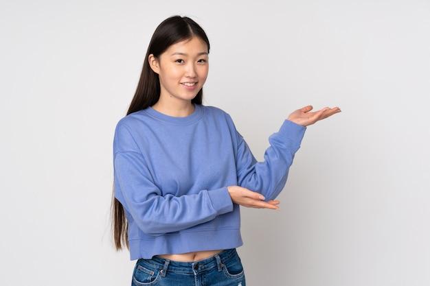 Giovane donna asiatica sulla parete che estende le mani al lato