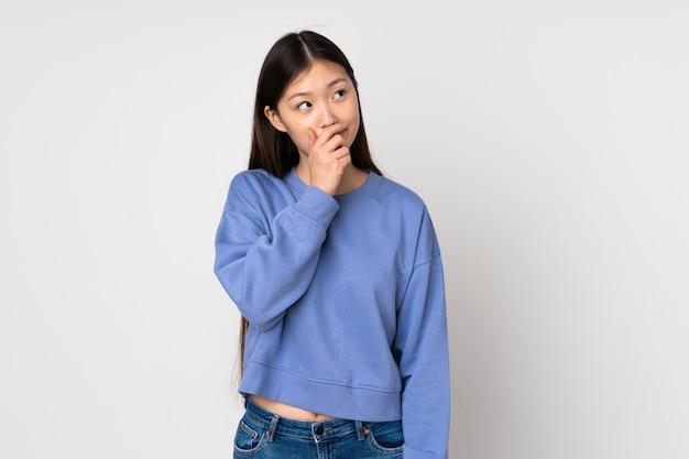 Giovane donna asiatica sulla parete che ha dubbi e con espressione del viso confuso