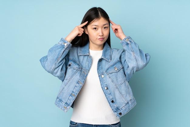 Giovane donna asiatica sulla parete che ha dubbi e pensiero
