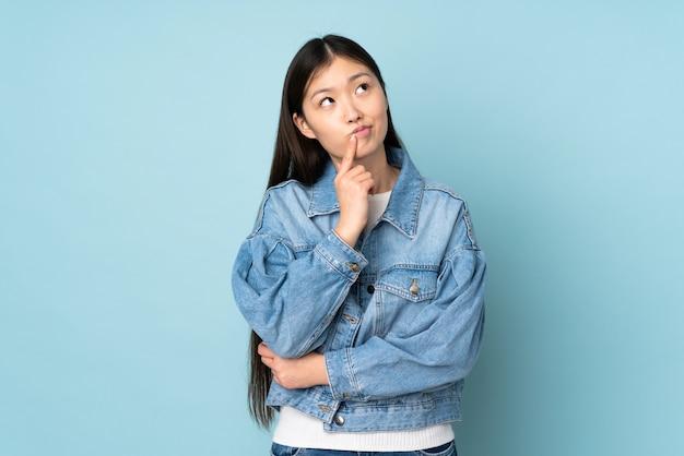 Giovane donna asiatica sulla parete che ha dubbi mentre osserva in su