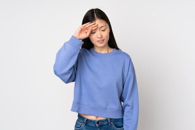 Giovane donna asiatica sulla parete con espressione stanca e malata