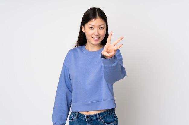 Giovane donna asiatica sulla parete felice e contando tre con le dita