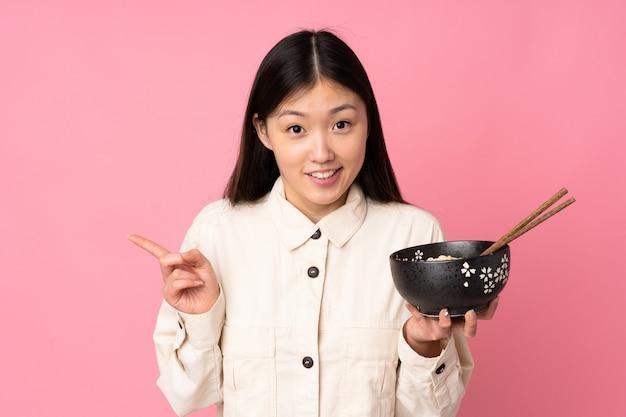 Giovane donna asiatica sulla parete rosa sorpresa e puntando il dito verso il lato mentre si tiene una ciotola di noodles con le bacchette