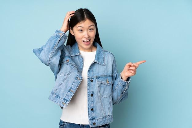 Giovane donna asiatica sulla parete sorpresa e puntando il dito verso il lato