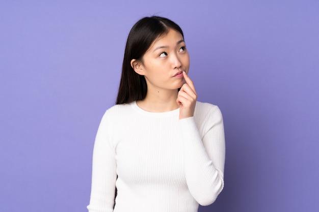Giovane donna asiatica sulla parete viola che ha dubbi mentre osserva in su