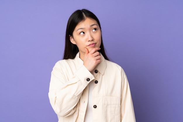 Giovane donna asiatica sulla parete viola che ha dubbi