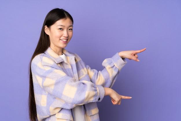 Giovane donna asiatica sulla parete viola che indica barretta il lato