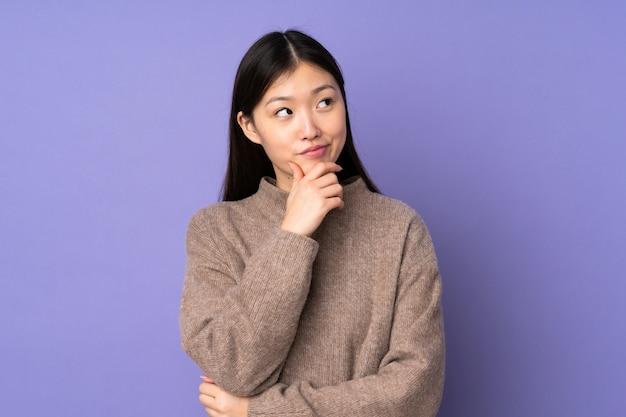 Giovane donna asiatica sulla parete viola che pensa un'idea mentre osservando in su
