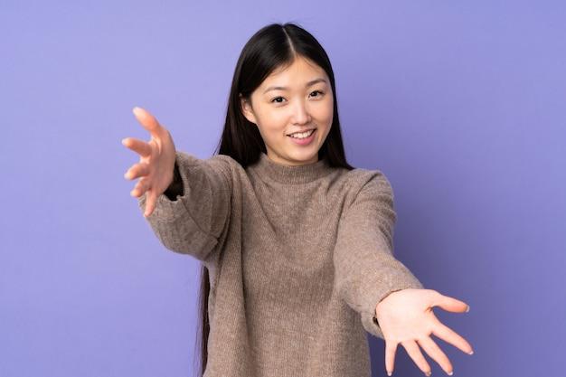 Giovane donna asiatica sulla parete viola che presenta e che invita a venire con la mano