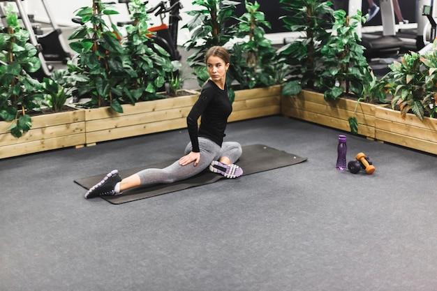 Giovane donna atletica che allunga la sua gamba in palestra