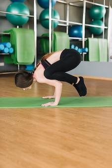 Giovane donna atletica che fa posa di yoga sulla stuoia verde di esercizio sopra il pavimento di legno