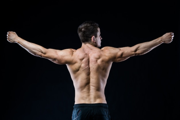 Giovane donna atletica che mostra i muscoli della schiena e delle mani